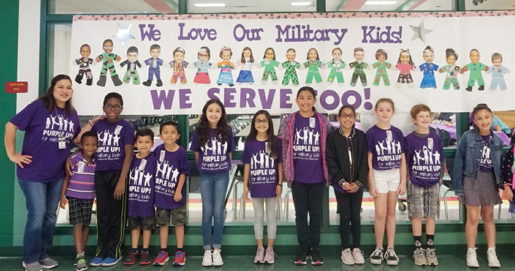 "Students in front of a banner that reads ""We love our Military Kids"""