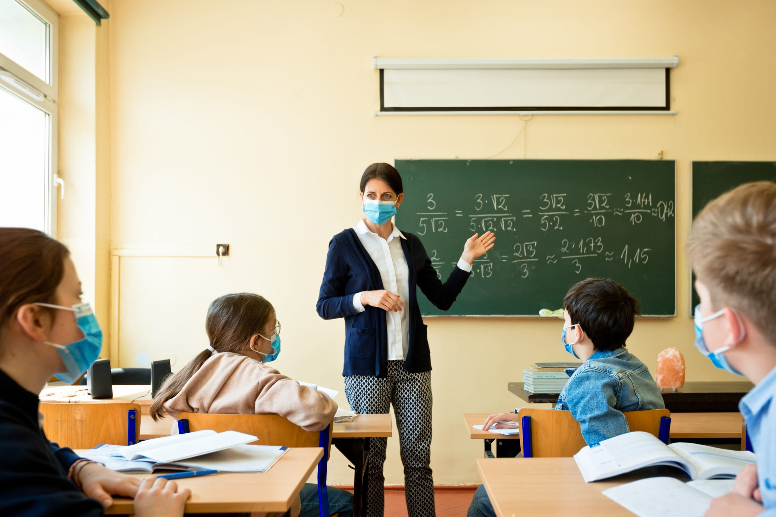 Teacher in mask teaching a group of students